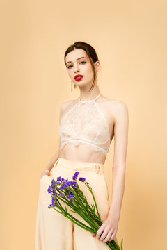 young woman holding limonium flowers and standing with hand in pocket isolated on beige