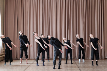 Horizontal shot of professional dancers wearing black outfit rehearsing their new contemporary dance