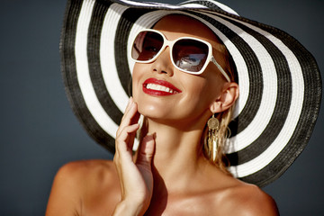 Beautiful smiling woman in hat and sunglasses - close up portrait