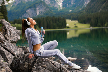 Young sports woman resting on a mountain next to the lake