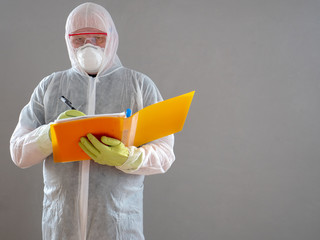 elderly man in protective overalls with orange folder and pen, special glasses and bactericidal mask. military pensioner ready to fight with coronovirus and treat the room with special solution