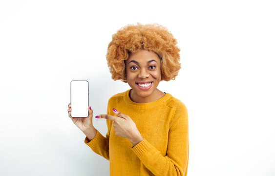 Portrait of a smiling African American woman showing mobile phone on white screen. Black joyful girl points to an empty smartphone.