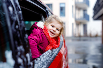 Cute adorable happy toddler girl sitting in car before leaving for winter vacations with parents. Little smiling child looking out from window and smiling. Baby wearing warm clothes