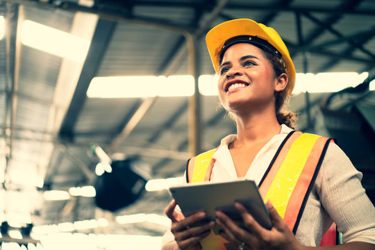 Portrait of industrial worker standing with tablet holding in her hand.