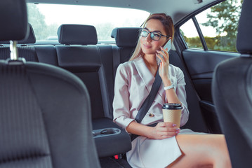 Beautiful girl secretary in business class of VIP taxi calling on phone, holding smartphone, fashionable and modern woman, cup of coffee with tea. Work on road, business meeting car. Meets passenger.