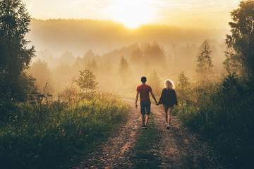 Young couple walking on the road. Fog covered the hills. Foggy morning.