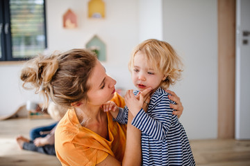 Wall Mural - Young mother with small daughter indoors in bedroom talking.