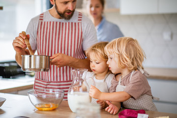 Wall Mural - Young family with two small children indoors in kitchen, cooking.