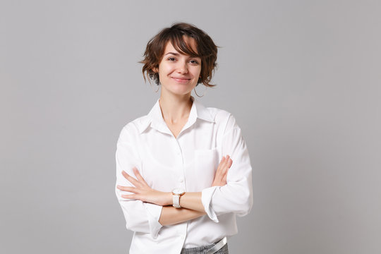 Smiling attractive young business woman in white shirt posing isolated on grey wall background studio portrait. Achievement career wealth business concept. Mock up copy space. Holding hands crossed.