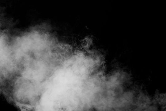 Isolated white fog on the black background, smoky effect for photos and artworks. Smoke and powder overlay on black background