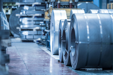 Industrial background. Big size steel coil stored inside industrial warehouse, blue toned image .