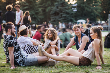 Obraz Group of young friends sitting on ground at summer festival. - fototapety do salonu