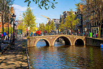 Wall Murals Amsterdam Stunning view of Amsterdam canals and typical dutch houses with narrow cosy streets filled with bicycles in the capital of Netherlands, Europe on a beautiful sunny day.