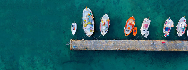 Aerial drone ultra wide photo of traditional fishing boat docked in old port of Mykonos island,...