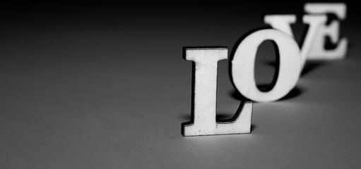 Fototapeta Litery tworzą słowo LOVE ustawione jeden za drugim, L z bliska, wyraźne, pozostale  oddalone i rozmyte, czarno-biale na szarociemnym tle obraz