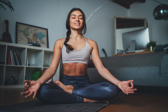 Young beautiful woman meditating at modern home interior sitting on yoga mat and smiling relaxed with closed eyes, Mindfulness meditation concept, Healthy Lifestyle
