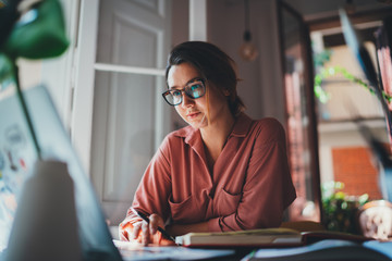 Pretty young woman an advertising copywriter in eyeglasses working at home using laptop, female graphic designer working in modern studio, Networking Freelancer Businesswoman Designer Entrepreneur Wall mural