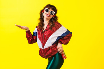 Cheerful gorgeous girl in clothes in the style of the 90s, with a vintage cassette player and headphones, in the studio on a white background. Music, emotions, fashion Wall mural