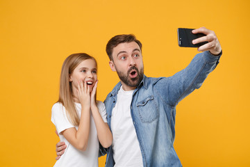 Shocked bearded man in casual clothes with child baby girl. Father little kid daughter isolated on yellow background. Love family day parenthood childhood concept. Doing selfie shot on mobile phone.