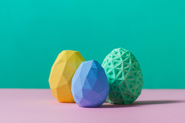 Color geometric Easter eggs on turquoise and pink background
