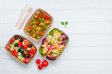 Fototapeta Vegetable salad in the brown kraft paper food containers on white wooden background obraz
