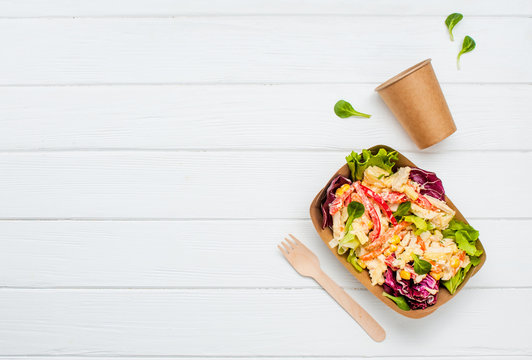 Vegetable salad in the kraft paper containers on white background with copy space