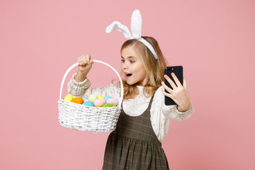 Little blonde kid girl 11-12 years old in spring dress bunny rabbit ears hold in hand cell phone wicker basket colorful eggs isolated on pastel pink background Childhood lifestyle Happy Easter concept