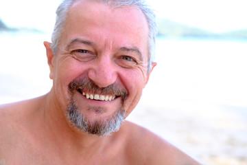 retired joyful man relaxing on the beach closeup portrait
