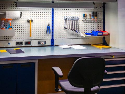 Cabinet car mechanic. A desktop in a car workshop. Tools hang over the desktop. Desk with drawers for tools. Concept - work in a car workshop. Career auto mechanic. Concept - vehicle inspection