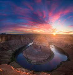 Beautiful Horseshoe Bend sunburst sunset and colorful clouds with reflections