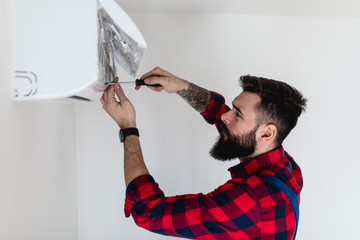 Young bearded handyman repairing air conditioner.