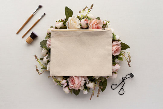 Blank canvas makeup bag mockup on a bright cream background with floral wreath - eco makeup bag / natural beauty concept mockup