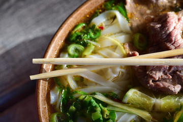Close-up of a typical Vietnamese dish, a pho with noodles, meat and vegetables, in a bowl with bamboo chopsticks on top