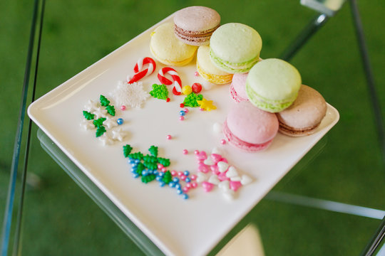 New Year's treats. New Year's cookies and macrons lie on a white plate.