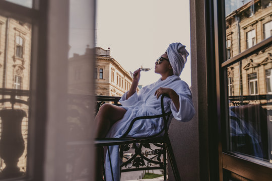 woman in bathrobe on the balcony while singing light wine