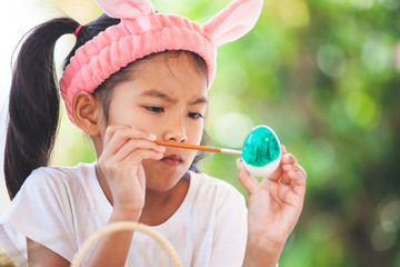 Cute asian child girl drawing and painting on easter eggs prepare for easter day in easter festive.