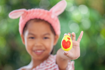 Happy asian child girl drawing heart picture on egg and holding painted easter egg with fun in easter festive.