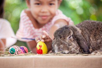 Cute Holland lop rabbit sitting on the table with asian child girl holding painted easter egg in background at easter festival