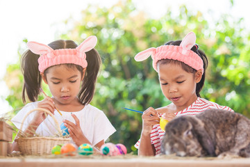 Two cute asian child girls drawing and painting on easter eggs together prepare for easter day. Children and Holland lop rabbit in at easter festive.