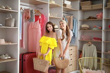 Beautiful young women choosing clothes from large wardrobe