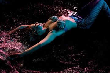 Woman in mermaid image lying in water dops shot
