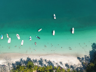 aerial top bottom drone picture with boats yachts and people playing at a beach in the pacific of Panama