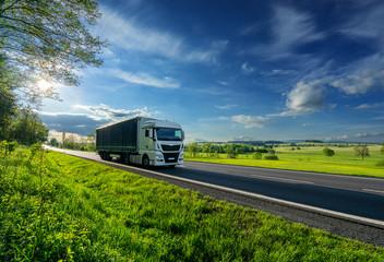 Fotobehang - White truck driving on the asphalt road in a spring rural landscape