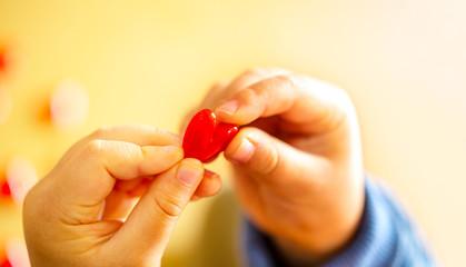 赤いハートのモチーフを持つかわいい子供の指のクローズアップとコピースペース