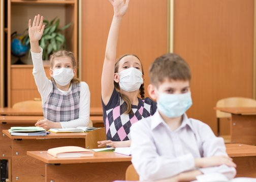 Schoolers students wearing protection mask to prevent virus on lesson in classroom