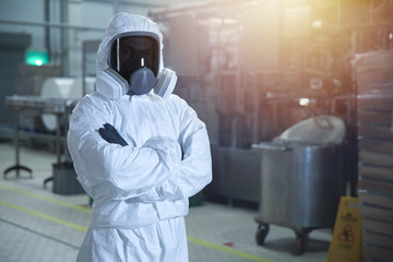 man in chemical protection clothes and toned mask in a factory against the background of an industrial workshop looking into the frame.
