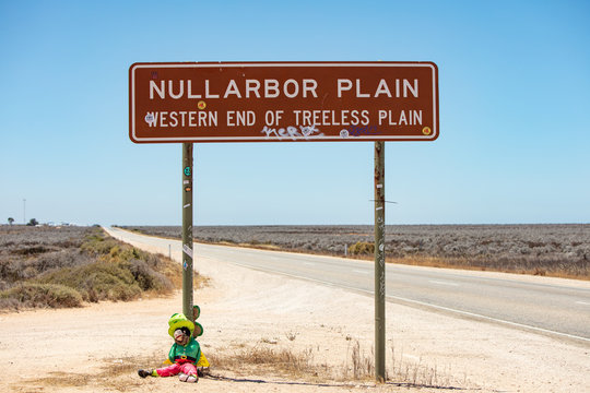 Leprachaun doll seated at the base of the famous Nullarbor Plain sign in Western Australia