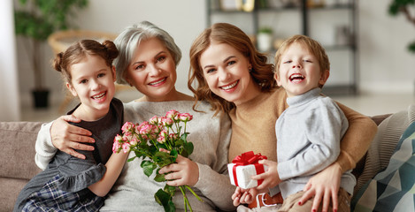 mother's day! three generations of  family grandchildren and children congratulate their mother and...