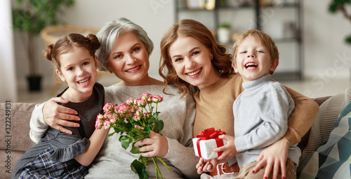 mother's day! three generations of  family grandchildren and children congratulate their mother and grandmother on the holiday and give flowers.