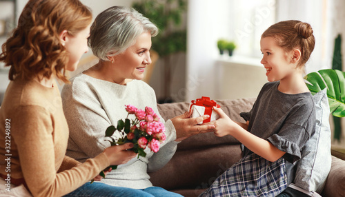 mother's day! three generations of  family mother, grandmother and daughter congratulate on the holiday, give flowers .